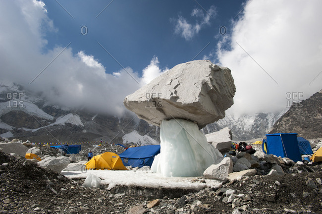 Khumbu Region, Nepal - April 14, 2009: Glacier holding large rock in the air surrounded by tents, Khumbu Region, Nepal, Himalayas, Asia