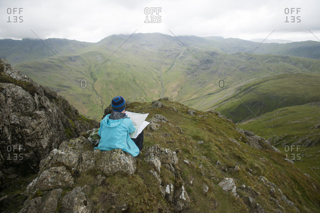A woman sitting near Stickle Pike in The Lake District to check her bearings on a map, Cumbria, England, United Kingdom, Europe