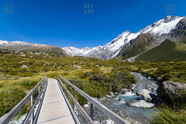 A hiking trail with a wooden bridge over a creak high up in the mountains, South Island, New Zealand, Pacific