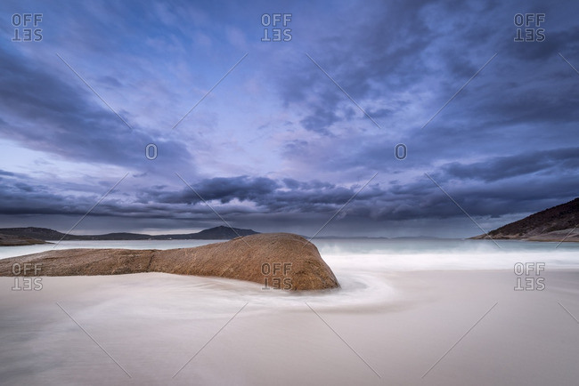 Sandy beach with rocks and spindrift in Western Australia