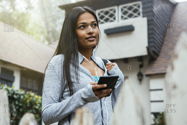 Woman listening to cell phone with ear buds