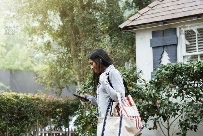 Woman carrying bags in neighborhood listening to cell phone with ear buds