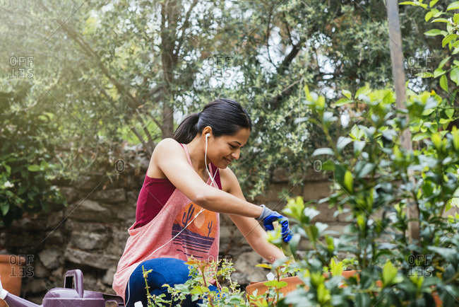 Woman listening to ear buds while gardening