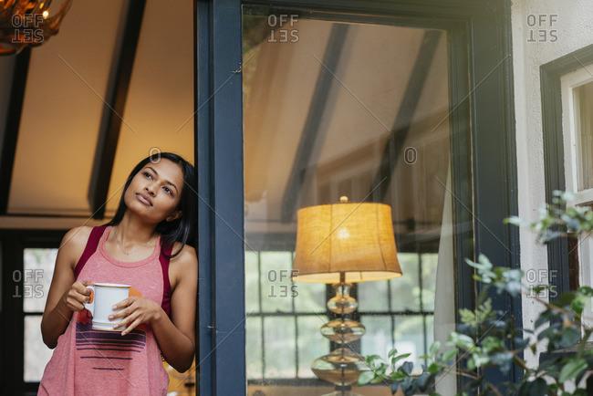 Woman daydreaming in doorway