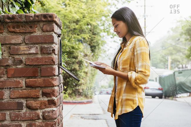 Woman reading mail at mailbox
