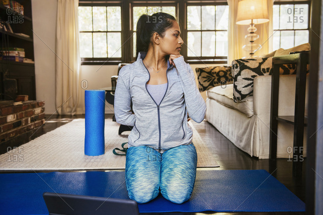 Woman kneeling on exercise mat stretching neck