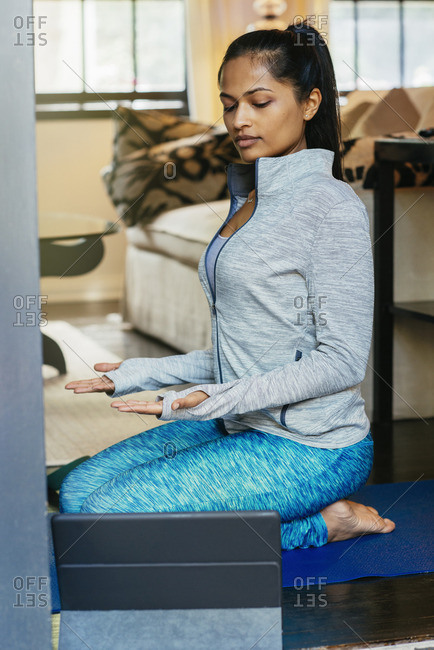 Woman kneeling on exercise mat meditating