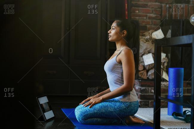 Woman kneeling on exercise mat