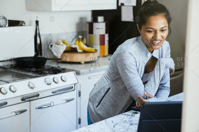 Woman video chatting on digital tablet in kitchen