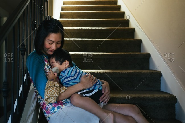 Asian mother holding son on stairs