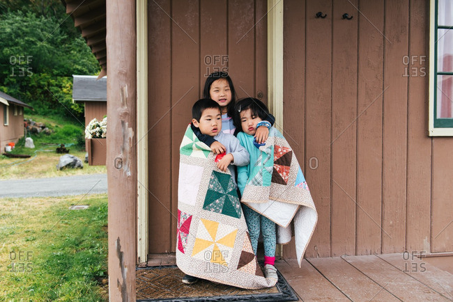 Siblings wrapped in quilt by cabin