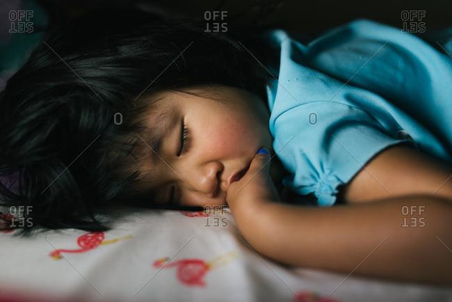 Asian girl asleep on a bed