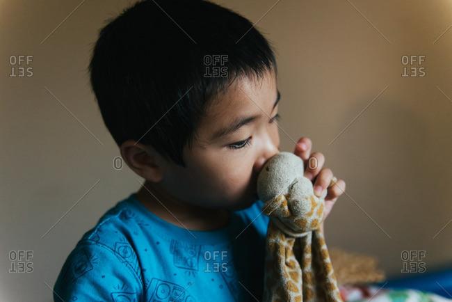 Boy sucking thumb holding stuffed animal