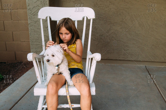 Girl and white terrier in rocking chair