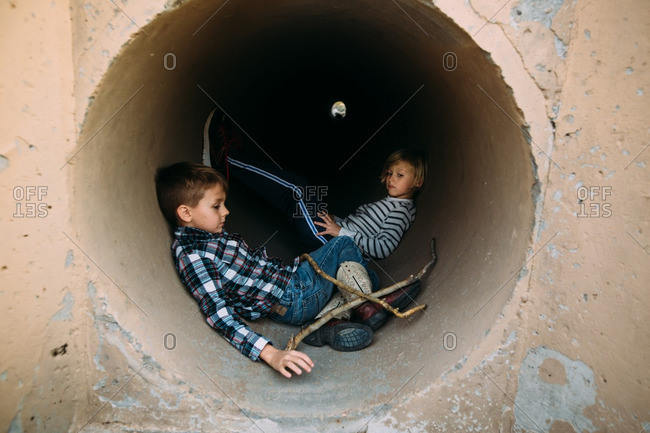 Two kids in concrete tunnel