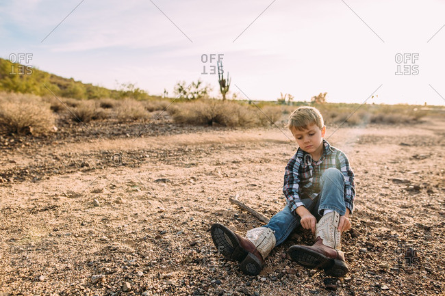 Boy putting on cowboy boots in desert
