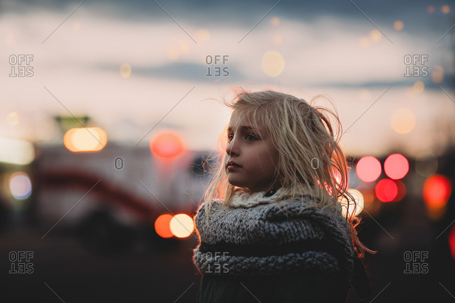 Girl in knit shawl with lights in background