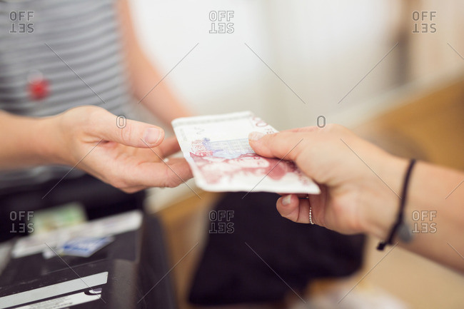 Money being given by one woman to other