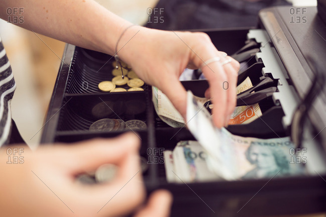 Woman taking money from cash register