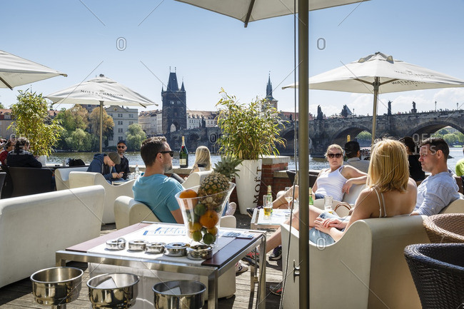 Prague, Czech Republic - May 7, 2016: People sitting at a cafe by the Vltava River with a view to the Charles Bridge, Prague, Czech Republic