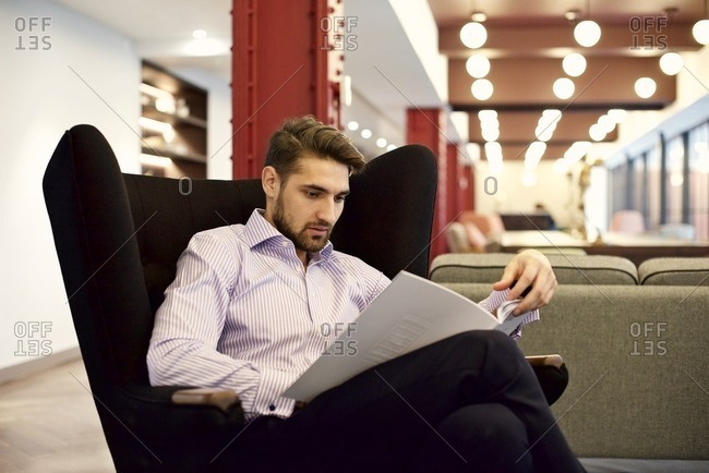 Young man in a modern office looking at paperwork