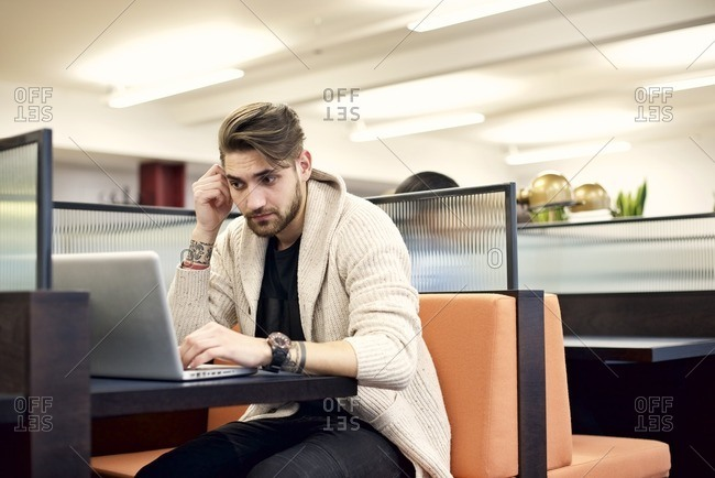 Young man sitting at a desk in a modern office using a laptop