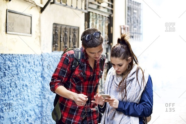 Young man and woman looking at a cellphone in a street