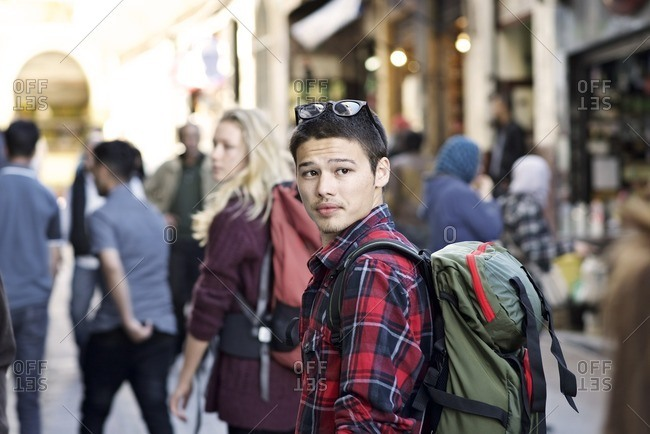 Young man with a backpack in a crowded street