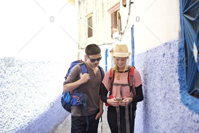 Young man and woman standing in an alley looking at a cellphone