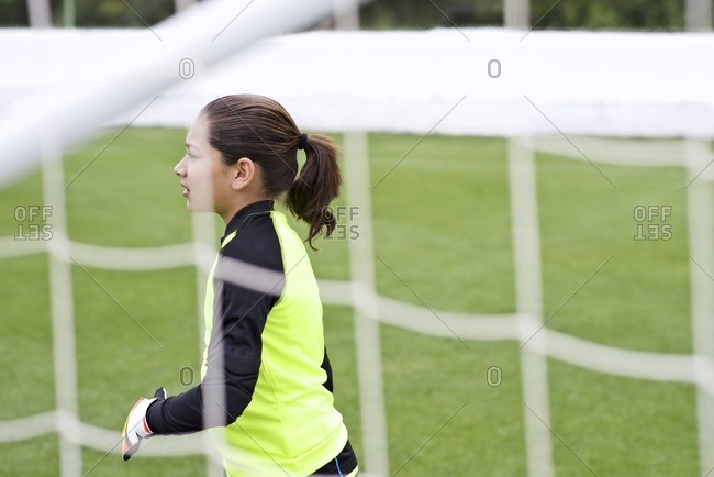 Girl standing near a goal on a soccer field