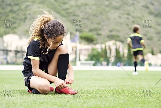 Young soccer player on a field tying her shoe