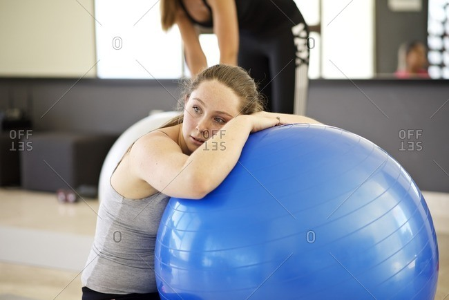 Young woman resting against a fitness ball