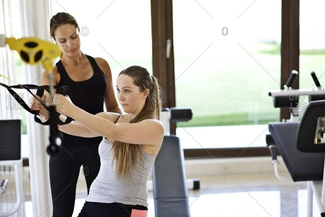 Personal trainer helping a woman exercise in a gym