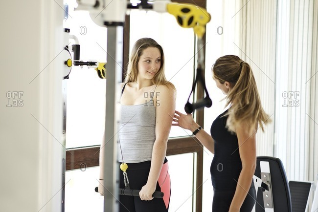 Trainer coaching a young woman at a gym