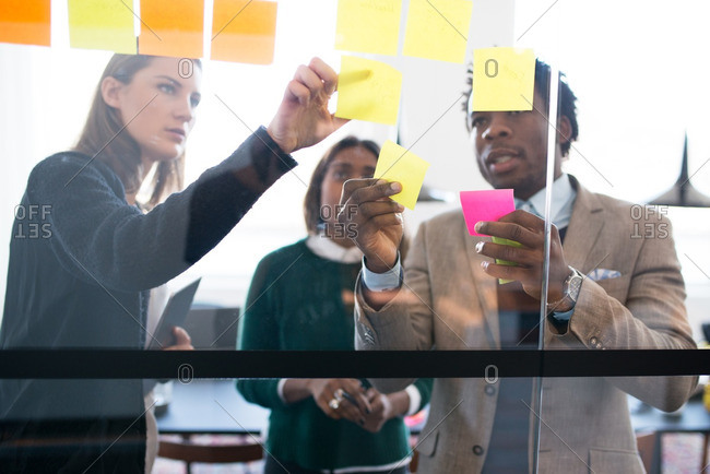Three coworkers organizing sticky notes in office