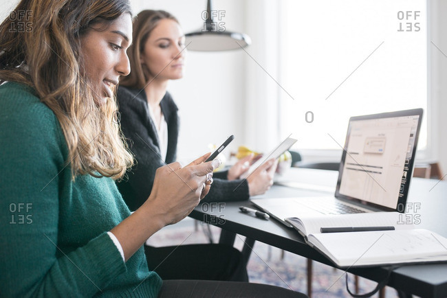 Female colleagues on devices in office