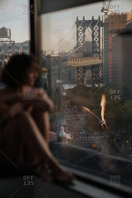 Woman gazing out bathroom window with view of Manhattan bridge