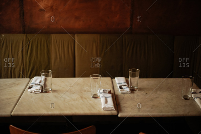 cafe tables set with glasses and silverware