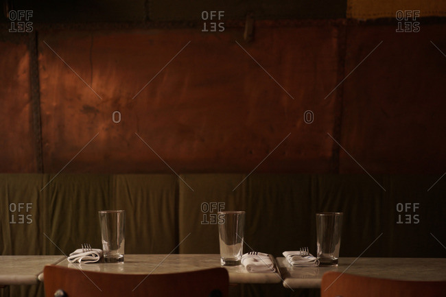 Restaurant tables set with glasses and silverware in restaurant