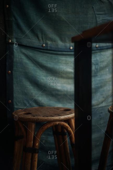 Vintage wooden cafe stools against denim cloth