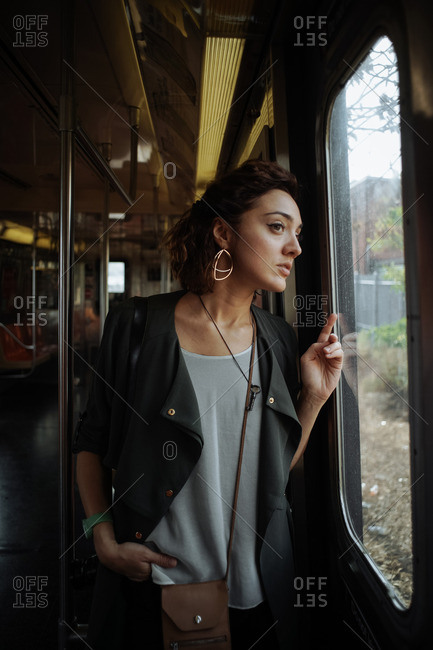 Woman looking out the window of a subway car
