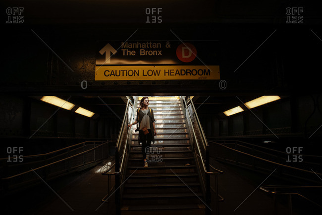 Woman walking down steps into a New York subway station