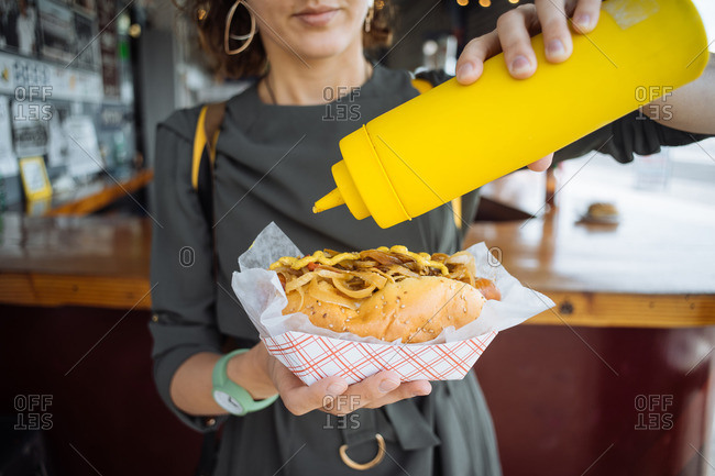 Woman putting mustard on a big hot dog in restaurant