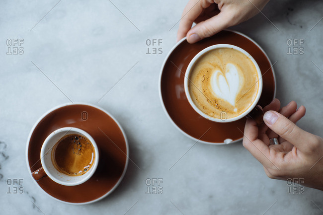 Hands holding cup of cappuccino on marble table with cup of espresso