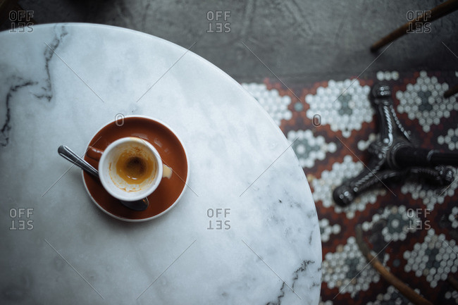 Overhead view of a finished cup of espresso on cafe table