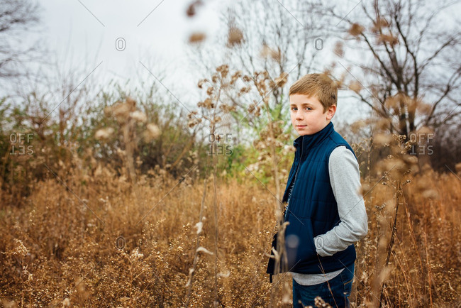 Boy standing in a tall overgrown field
