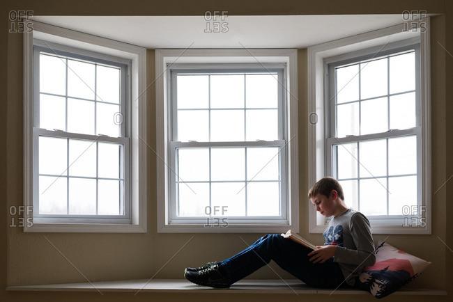 Boy sitting in a window seat reading a book