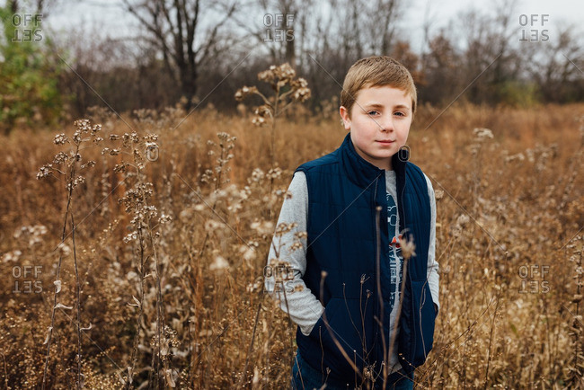 Boy standing with his pockets in an overgrown field