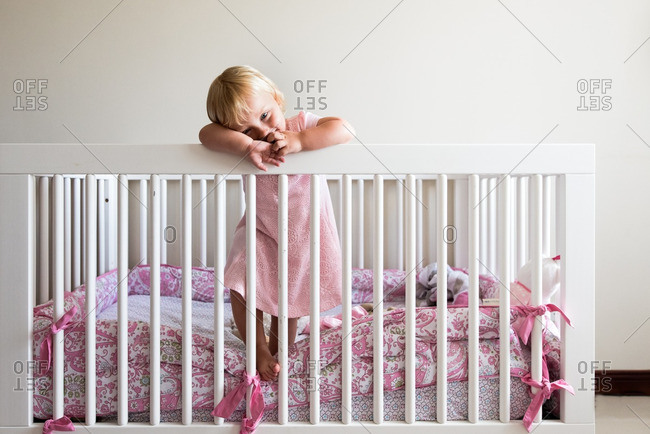 Toddler girl leaning on crib railing
