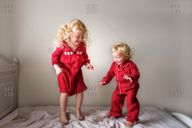 Two blonde girls jumping on bed